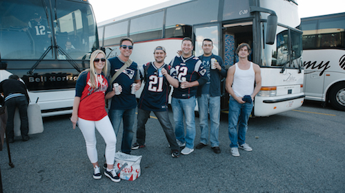 patriots fans tailgating in front of a bus