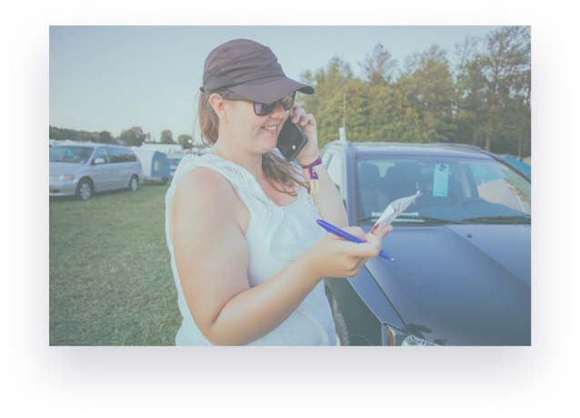 woman answering a phone call and taking notes while at a festival
