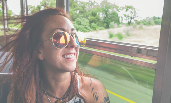 smiling girl with sunglasses riding a bus and looking out the window